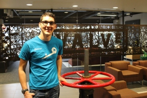 Kristian Miller, a 2011 graduate of MSU and current master's student, stands next to the eponymous valve in the main lobby of Valve Software. Photo By Brent Zundel