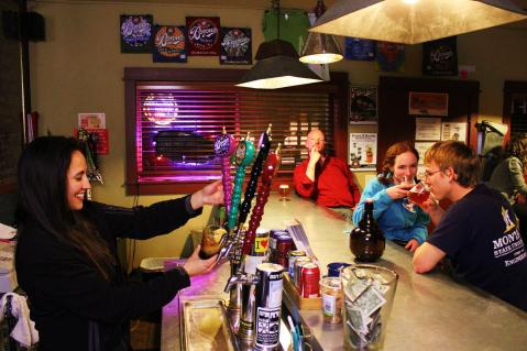 MSU students Bronwyn Rolph and Chris Zimny enjoy locally brewed beers at the Bozeman Brewing Company taproom, while bartender Mitzi Kuall pours a pint. Photo by Brent Zundel