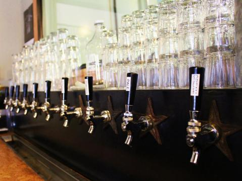 Pint glasses and growlers wait to be filled above the taps at Outlaw Brewing in Belgrade, Mont. Photo by Brent Zundel